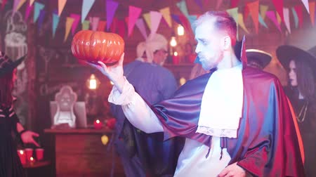 madness : Man in a ghoul or vampire costume is dancing with a jack-o-lantern in his hand
