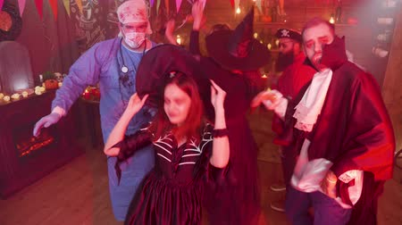 disfarçar : Teenage girl in evil witch costume dancing in the middle of a group of friends celebrating halloween. Gang of friends in scary outfits having fun at a party. Vídeos