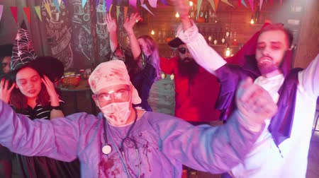dança : Man in evil doctor costume dancing in the middle of a group of friends celebrating halloween. Gang of friends in scary outfits having fun at a party.