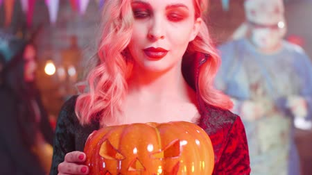 disfarçar : Close-up shot of a young sensual woman in the costume of a vampire at a halloween party. Vampiress holding a jack-o-lantern in her hands.