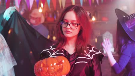 disfarçar : Teen girl in evil witch costume with a jack-o-lantern in her hands. Scary characters dancing at a halloween party. Vídeos