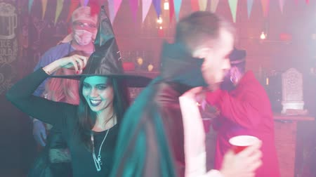 disfarçar : Young people drink and dance at a halloween party in a local pub. Gang of friends dancing and having fun diguised in scary costumes.