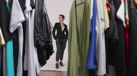 professional photography : Shooting through a rack of clothes ready for the photo shoot. Professional model posing on white background Stock Footage
