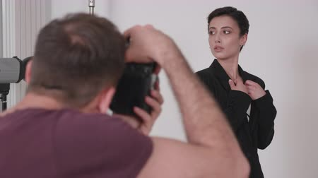 oturum : Over the shoulder shot of professional photographer taking pictures of a model in studio on a white background