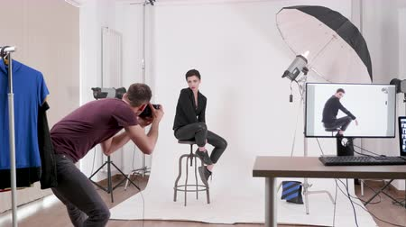 profi : Model posing in fashion style to a professional photographer in a well lit photo studio Stock mozgókép