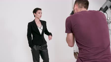 fotográfico : Professional photographer taking a lot of pictures to a model in a studio over a white background Stock Footage