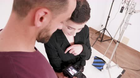 atirar : Professional photographer and model looking at pictures on camera screen in studio Stock Footage
