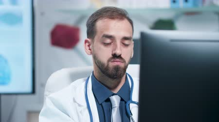 tiredness : Close up shot of tired and exhausted doctor working on the computer