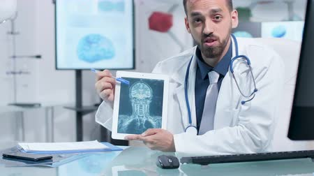 назначение : Doctor showing a X ray scan on a digital tablet PC and talking about it. Modern research facility with 3D brain scans running in the background