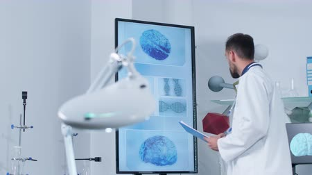 рентгенологическое : Dolly shot of a scientist in modern research center looking at big TV with 3D models of brain and DNA string. He is taking notes in the clipboard Стоковые видеозаписи