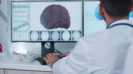 tomography : Handheld shot of doctor in front of 3D brain scan displayed on computer monitors in modern research facility