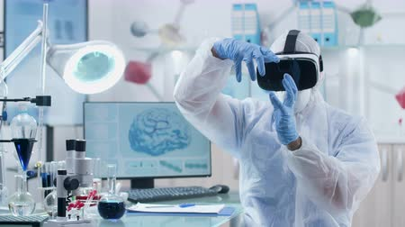 proveta : Scientist wearing VR headset in professional laboratory is working in virtual reality. Modern research and technology Vídeos