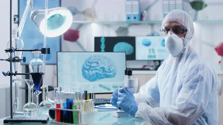 kimyager : Concentrated chemist wearing protective mask, clothes and glasses looks at the camera. Modern research center with displays showing 3D scans of brain and DNA strings