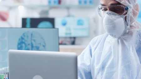 farmacologia : Close up shot of researcher face wearing a protective mask and glasses working in professional modern high end laboratory