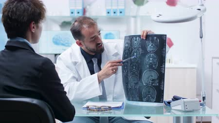 x ray image : Doctor at desk in modern research facility showing X ray scans to patient. In the background - monitors displaying 3D brain simulations and DNA strings Stock Footage