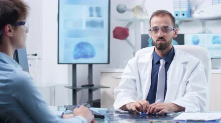 surgical light : Doctor with AR glasses showing something to a patient. In the background - modern and high end research facility with screens running brain simulations
