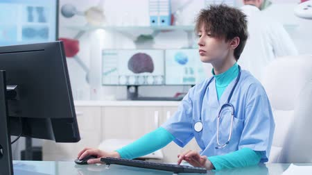 pacientes : Young nurse typing on computer keyboard in high end tech research center while the doctor is conducting studies on the computers in the background