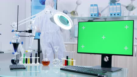 tesisler : Dolly shot of high end secure research facility with a green screen monitor on the desk in the front. A scientist in coverall is working in the background
