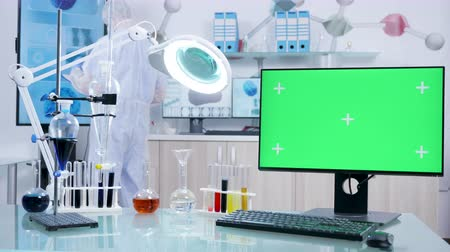 tomography : Dolly shot of chemist desk with a green screen computer. A scientist walks in the facility Stock Footage