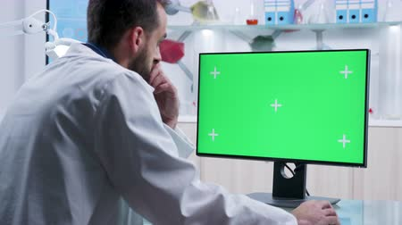 asistan : Dolly shot of practitioner typing on computer with green screen in a modern and high end research facility