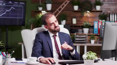 servet : Businessman reading an important email, happily reacts. in the background - modern office with creative design and screens displaying animated charts and data. Slow motion footage