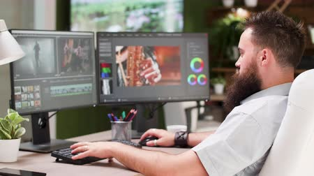 digitální : Bearded guy work as video editor or colorist in creative media agency. In the background - modern office with big TV displaying footage