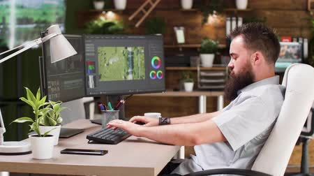 editor : Video editor working in professional software. He uses a dual screen setup and works in modern designed studio office