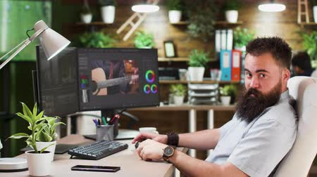 creator : Portrait of male video editor or colorist working in cozy and stylish office. He has a dual screen setup and uses software modern software