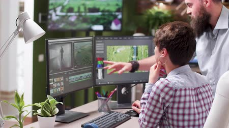 creator : Handheld shot of professional video editor at her workstation talking with a colleague. Professional video editing and coloring software