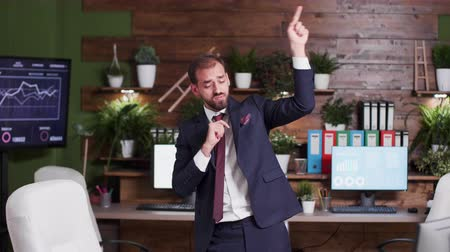 выражающий : Silly businessman dances happily in cozy and nice looking office