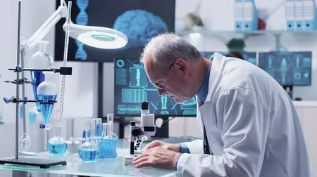 genetic research : In modern laboratory scientist is looking at samples through a microscope. The screens are displaying futuristis medical HUDs Stock Footage