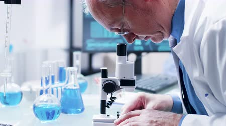 farmacologia : Close up shot of researcher in his 60s looking in a microscope
