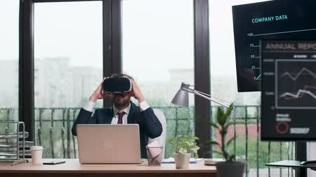 alcançando : Businessman in formal suit puts ON a VR headset. Modern office with big windows. Rainy day