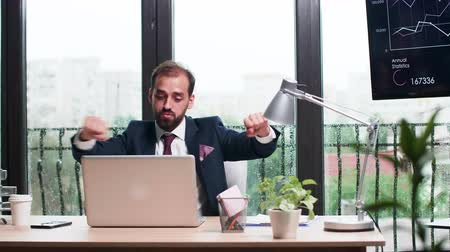 humor : Businessman dances happily at his desk in modern office with big windows. Rainy day outdoor