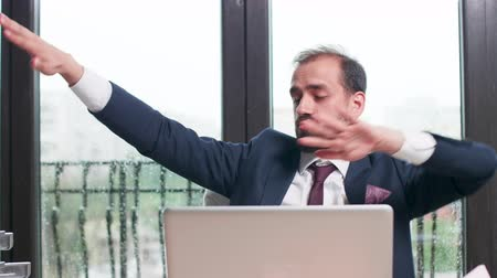 humor : Close up shot of happy business worker dancing at his desk in an office with big windows. Rainy day outside Stock mozgókép