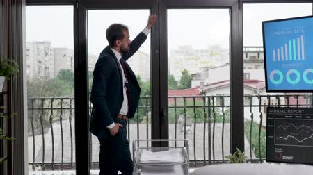 think big : Businessman sitting near the big windows of his office looking outside and thinking. Slow motion footage Stock Footage