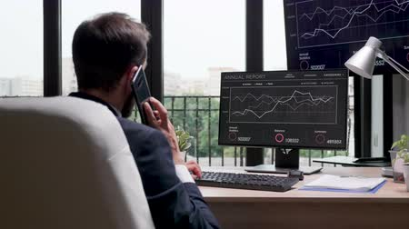 think big : Revealing shot of businessman working on the computer in modern office with big windows. Display shows sales statistics