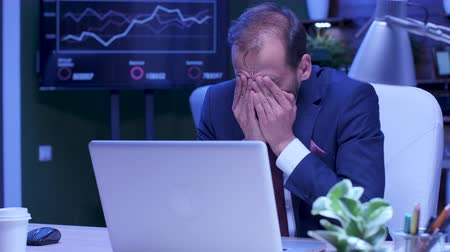 tezgâhtar : Exhausted man in formal suit works on the laptop late at night in the office Stok Video