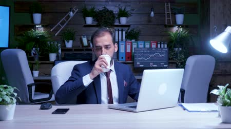 gerir : Zoom in shot of businessman working late at night in the office. He drinks coffee to stay awake