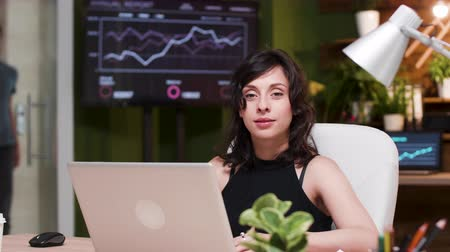 неформальный : Young businesswoman sitting at the desk, lookint at camera and smiling