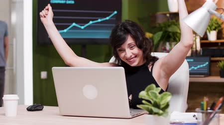 humor : Excited female corporate worker reads good news on the laptop. Slow motion shot in cozy nice office Stock mozgókép