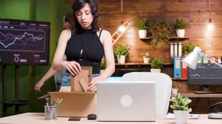 belongings : Beautiful woman getting fired from the job. She packs her belongings in a cardboard box and leaves the office