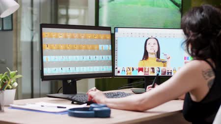 редактировать : Over the shoulder shot of professional female photographer working in editing software or application on her dual monitor setup. Creative media agency