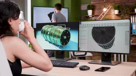 dizayn : Over the shoulder shot of professional designer working on new turbine prototypes in 3D software. Slow motion zoom in shot