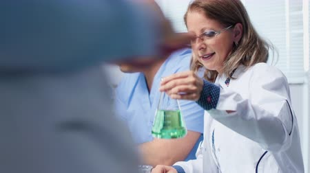 kiełki : Female laboratory engineer working with her assistant in modern and high end biochemistry lab