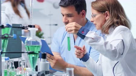pipet : Assistant is taking notes from a senior biotechnologist in modern and high end laboratory Stok Video