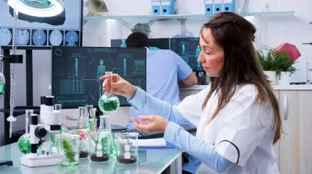 pipet : Female chemist researcher testing some green samples in modern laboratory Stok Video