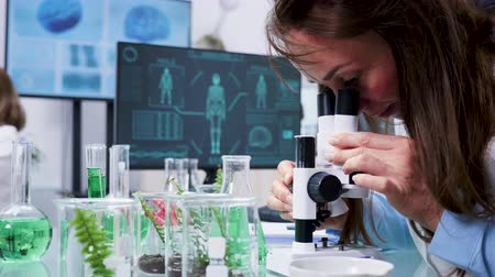pipette : Close up shot of female biologist looking into the microscope in modern high end laboratory