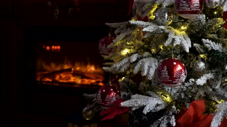bola de fogo : Gorgeous decorated Christmas tree and a fireplace in the background Stock Footage