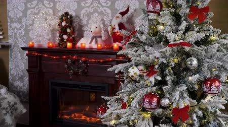 bola de fogo : Static shot of Christmas tree full of garlands next to a fireplace in cozy home